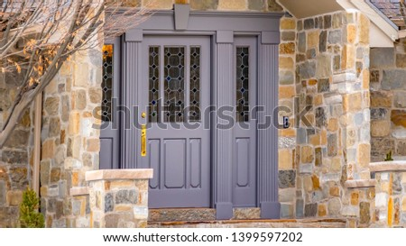 Panorama Facade of a home with a beautiful stone wall and gray front door #1399597202