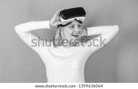 Woman using VR device. Pretty woman playing game in virtual reality glasses. Beautiful woman wearing virtual reality goggles in studio. Simulation game #1399636064