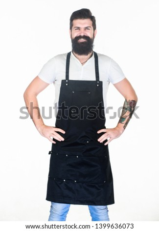 Let my happy smile warm your hearts. Happy man wearing barber or cooking apron. Bearded man happy smiling in bib apron. Brutal hipster with happy smile on unshaven face. #1399636073