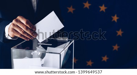 Elections to the European Parliament. EU elections. Man throwing his vote into the ballot box. #1399649537