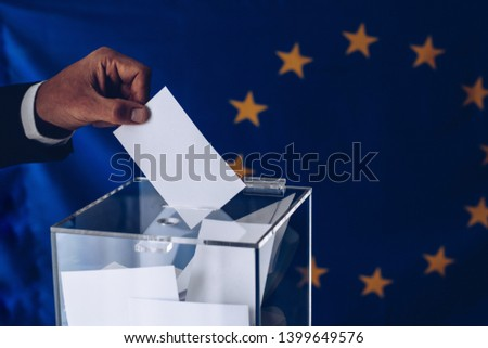 Elections to the European Parliament. EU elections. Man throwing his vote into the ballot box. #1399649576