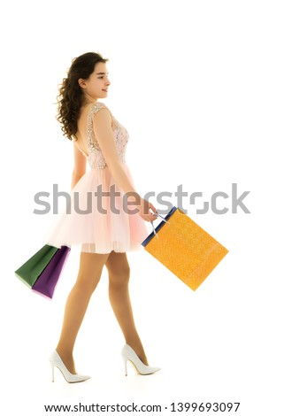 Beautiful teen girl shopping in a store. With large paper bags in hand. The concept of holiday sales, advertising products. Isolated on white background. #1399693097