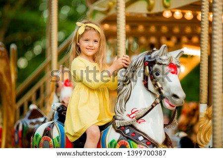 Adorable little girl near the carousel outdoors in Paris, baby girl on the carousel, Happy healthy baby child having fun outdoors on sunny day. Family weekend or vacations Royalty-Free Stock Photo #1399700387