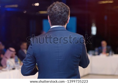 Young businessman at business conference room with public giving presentations. Audience at the conference hall. Entrepreneurship club. #1399735223