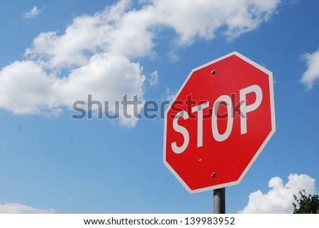 Red Stop Sign with Blue Sky and Clouds Background