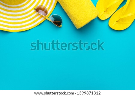 yellow beach accessories on turquoise blue background - sunglasses, towel. flip-flops and striped hat. summer is coming concept with copy space. holiday by the sea concept. #1399871312