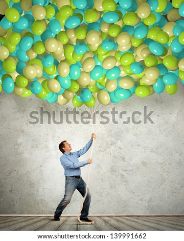 Image of adult man pulling rope with bunch of colorful balloons