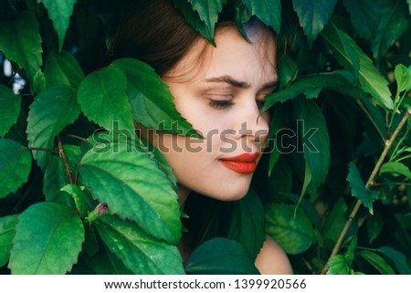 a woman with bright make-up and eyes closed hid in green bushes in nature                          #1399920566