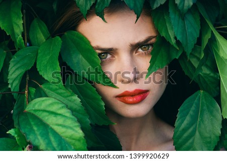 Beautiful woman with bright makeup hid in the bushes in the park #1399920629