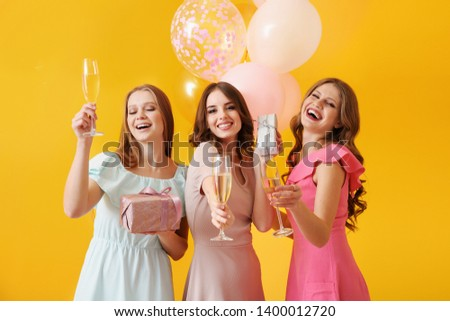 Beautiful young women with glasses of champagne and gifts on color background #1400012720