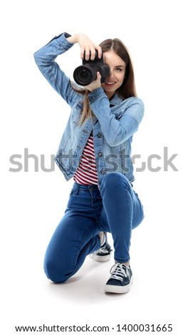 Young female photographer on white background