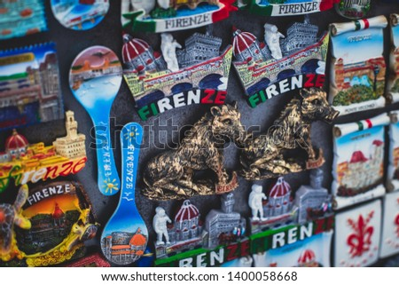 """View of traditional tourist souvenirs and gifts from Florence, Tuscany,  Italy with toys, masquerade masks, fridge magnets with text """"Florence"""" and key ring keychain, in local vendor souvenir shop #1400058668"""