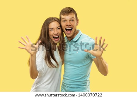 Beautiful young couple's half-length portrait on yellow studio background. Woman and man in shirts caddling and show the gesture of Hello. Facial expression, human emotions concept. Trendy colors. #1400070722