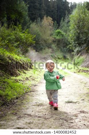 Little girl walks in the spring forest. #1400082452