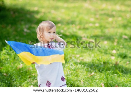Child carries fluttering blue and yellow flag of Ukraine in field. Ukraine's Independence Day. Flag Day. Constitution day. Girl in traditional embroidery with flag of Ukraine #1400102582