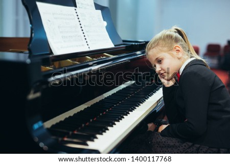 disappointed little girl trying to teach to play piano #1400117768
