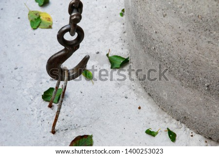 Large metal hook hooked on concrete structure #1400253023