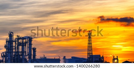 Petrochemical plant or oil and gas refinery industry with smoke stacks in silhouette image on sky sunset background #1400266280