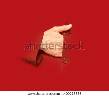 A male hand gets into the suit as Bonaparte Napoleon used to. Isolated hand on red bacground. The hand of a strategist. Conceptual image design. Royalty-Free Stock Photo #1400293553