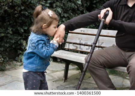 Little baby girl kiss her grandfather's hand during Eid mubarak (Turkish Ramazan or Seker Bayram). Adorable child kiss elderly man hand to show respect. Cute toddler follow muslim Ramadan traditions.