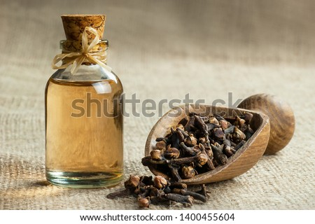 Close up glass bottle of clove oil and cloves in wooden shovel on burlap sack. Essential oil of clove rustic style background spice concept  #1400455604