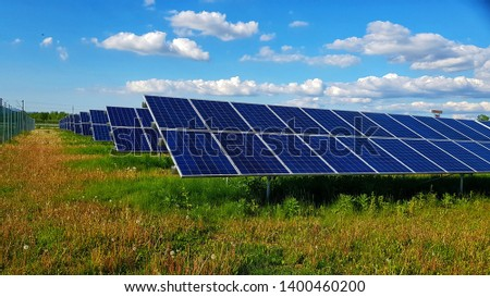 Photovoltaic panels or solar panels on a field with an amazing blue sky with clouds  #1400460200