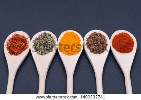 Collection of spices in wooden spoons (Saffron, Basil, Turmeric, Caraway seeds, Sweet Paprika) on dark background. #1400532761