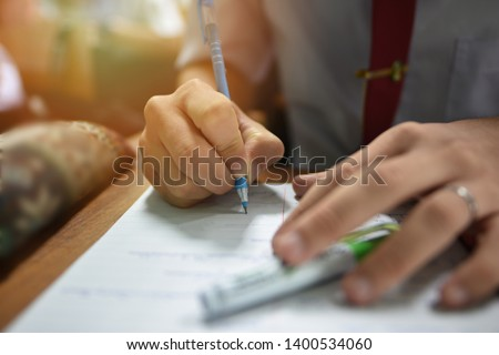 Student holding a pen taking lecture note or doing writing assignment in the classroom; closed up photo of young learner using a pen during the written test in collage or university training center #1400534060