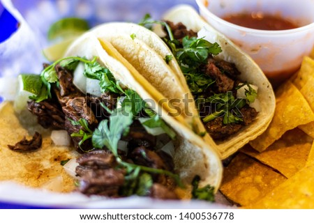 Two carne asada tacos with cilatro and onion on corn tortillas.