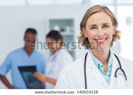 Woman doctor smiling and looking to the camera while a medical team is working #140054158