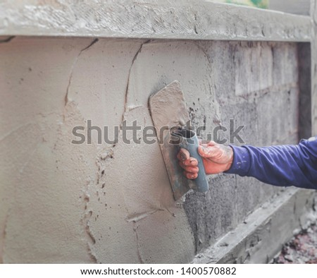 Mason plastering the concrete to build wall, Construction   #1400570882