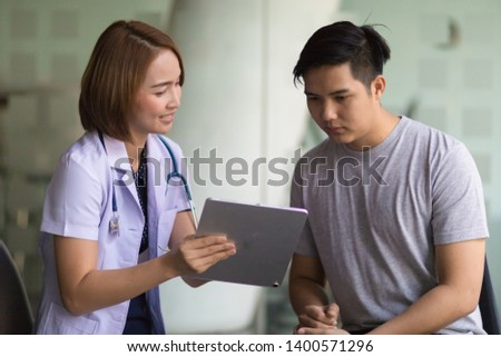 Asian female doctor using tablet computer and talking to male Asian patient #1400571296