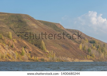 Autumn landscape, river, windy weather, dark blue water, yellow-red autumn leaves on trees, last warm days #1400680244