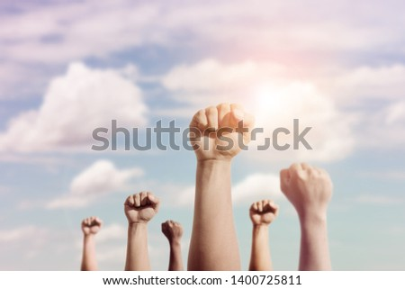 Celebration victory, success and winning concept.group of raised hands fist on blurred sky as backround #1400725811
