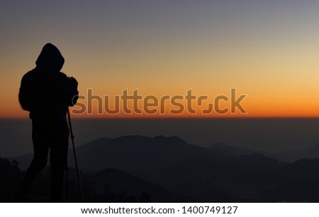 silhouette of Travel photographer standing with a camera mounted on a tripod and shooting a time lapse of the sunrise/sunset. man wearing his hood enjoying the mountain view /valley view #1400749127