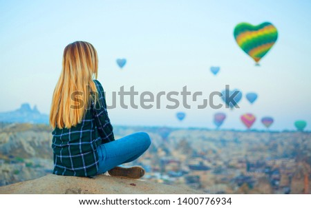 Woman watching wonderful view of a colorful hot air balloons in the shape of the heart flying over the valley at Cappadocia, Turkey. Concept of love for Turkey or love for travel #1400776934