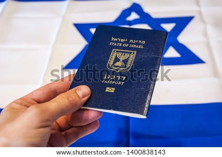 "Hand holding the passport of the State of Israel, Israeli flag on the background. Israel citizenship concept, Israeli biometric ""darkon"" passport illustrative image. #1400838143"
