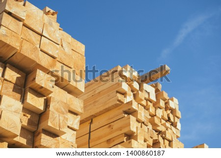 Wooden boards, lumber, industrial wood, timber. Pine wood timber stack of natural rough wooden boards on building site. Industrial timber building materials #1400860187