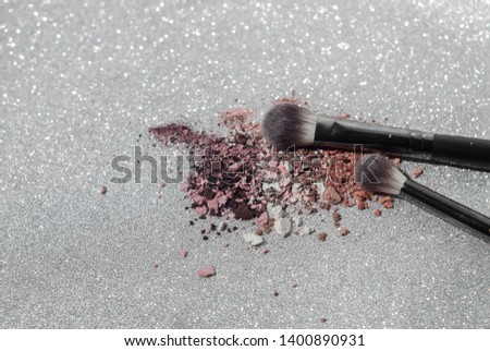 Make up brushes with colorful crushed eyeshadow on the silver glittery background. #1400890931