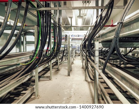 Power cables and instrument cables were installed with cable trays in electric cable room of power plant which show metal material of tray and black high voltage cable. #1400927690