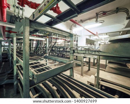 Power cables and instrument cables were installed with cable trays in electric cable room of power plant which show metal material of tray and black high voltage cable. #1400927699