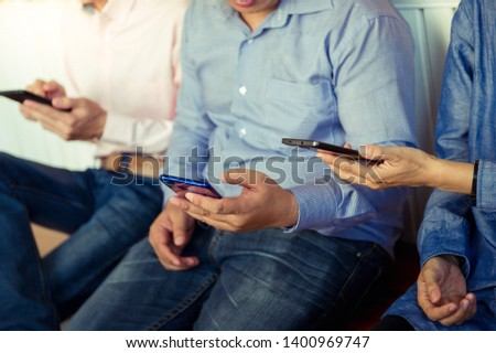 A group of friends who enjoy playing smartphones that are used to communicate, play games, technology concepts. Phone sticking #1400969747
