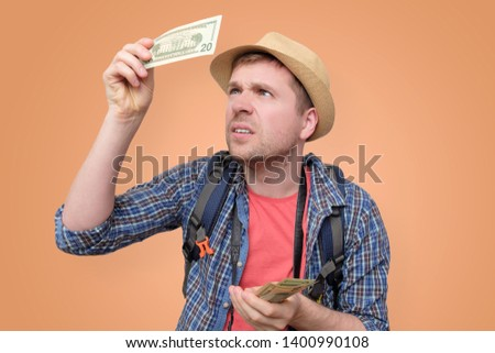 A man tourist in hat holds dollar bank note checking it for watermark. See through money. Verification of bills on vacation travelling.