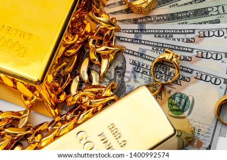 Jewelry buyer, pawn shop and buy and sell precious metals concept theme with a pile of cash in US dollars, golden rings, necklace bracelet and gold bullion isolated on white background #1400992574