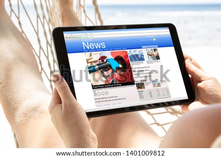 Close-up Of A Woman Lying On Hammock Watching News On Digital Tablet At Beach #1401009812