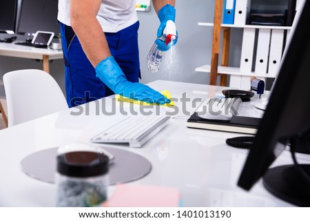 Janitor cleaning white desk in modern office Royalty-Free Stock Photo #1401013190