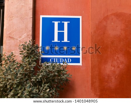 """Blue four stars hotel sign with """"city"""" written in Spanish against orange background"""