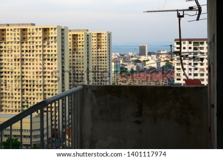 complex buildings aligned with television antenna before and sea behind #1401117974