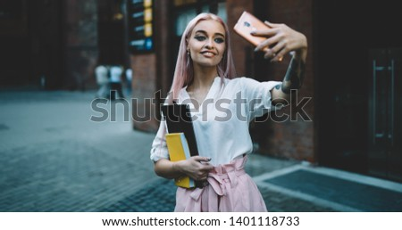 Happy female schooler with beautiful pink hair holding textbook for education and smiling while clicking selfie pictures via front camera on cellphone, cheerful millennial posing and taking images