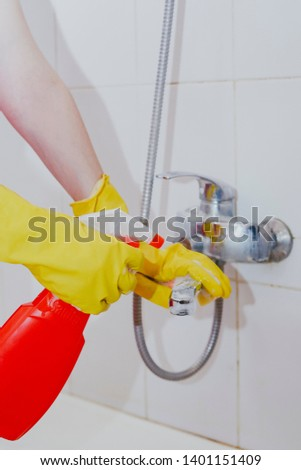 Housewife cleaning bathroom tap and shower Tap. Maid in yellow protective gloves washing dirty bath tap. Hands of woman washing or cleaning up bath #1401151409